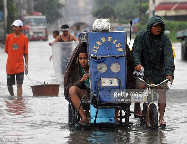 Residents wade through a flooded street caused by heavy rains overnight due to storms in Malabon City in suburban Manila on July 17 2009 Overnight...