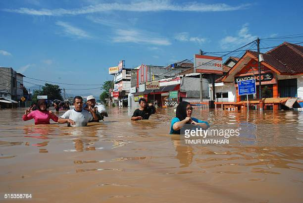 Residents wade through a flooded street in Bandung West Java on March 13 2016 Thousands of people fled their homes as the Citarum river overflowed in...