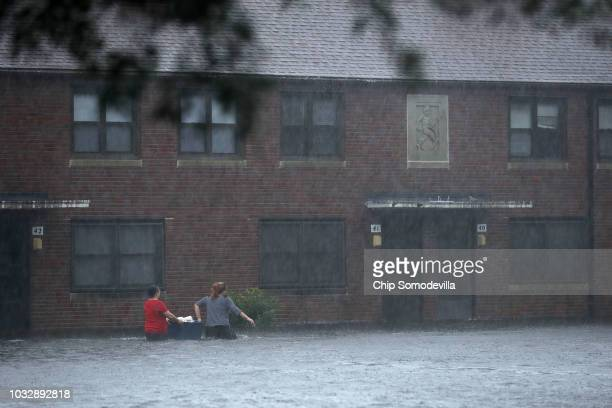 Residents wade through deep floodwater to retrieve belongings from the Trent Court public housing apartments after the Neuse River went over its...