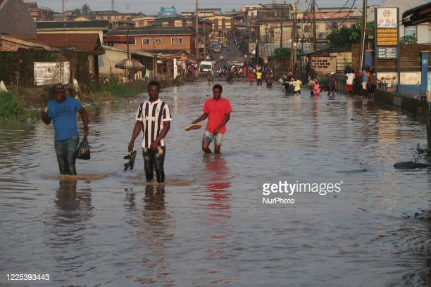 Residents wade through flooded Ige Road, Aboru, Lagos. Flood disrupted movement and socio-economic activities at Alabede area of Ige Road, Aboru,...