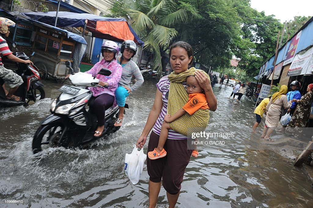 Residents wade through flooded neighborhood to reach relief distribution centers in Jakarta on January 24, 2013. Indonesia's National Disaster Mitigation Agency (BNPB) said more than 30,000 people were displaced while 20 people died during the widespread flooding that hit Jakarta as the weather bureau forecast more rains in the coming days.