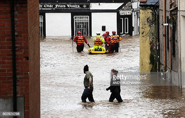 Residents wade through floodwater as members of the emergency services use a dinghy in a street in Dumfries southern Scotland on December 30 2015...