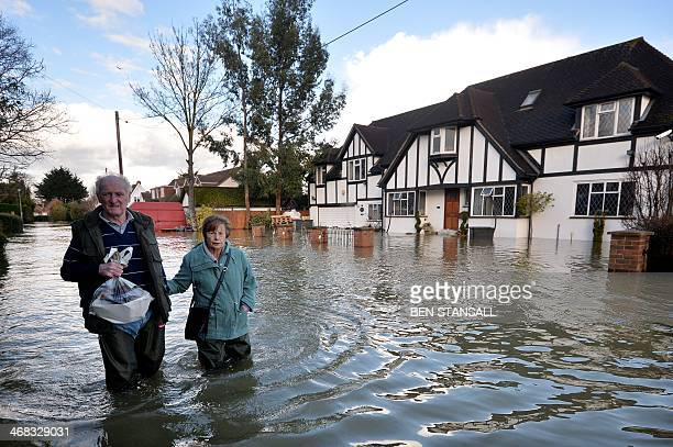 Residents wade through floodwater in the village of Wraysbury in Berkshire South East England on February 10 2014 Thousands of homes in southeast...