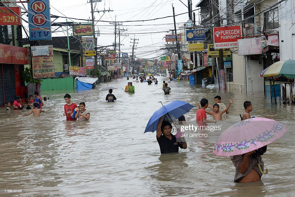 Residents wade through floodwaters in the farming town of