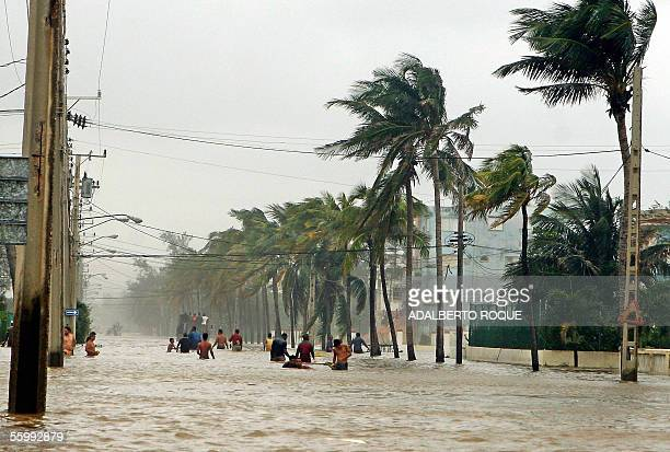 Residents wade through the water in Havana's north coastal 24 October 2005 after the devastating passage of Hurricane Wilma on its way to Florida...