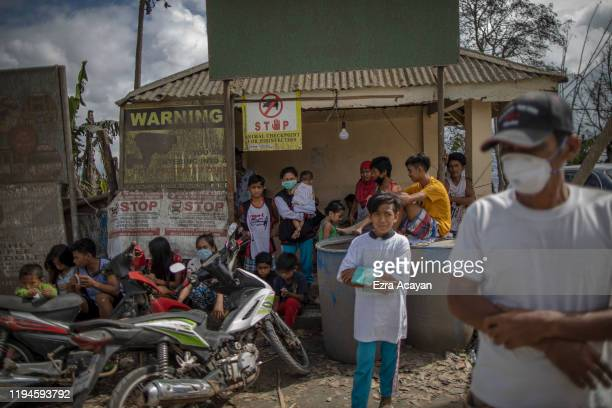 Residents wait along a highway for relief goods on January 19 2020 in the village of San Guillermo Talisay Batangas province Philippines The...