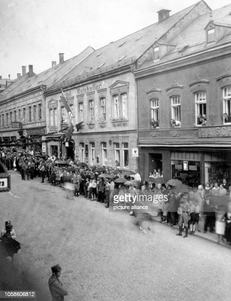 Residents wait along the sides of the street for the SA in Falkenstein near Auerbach, Germany, 1931. Photo: Berliner Verlag / Archive