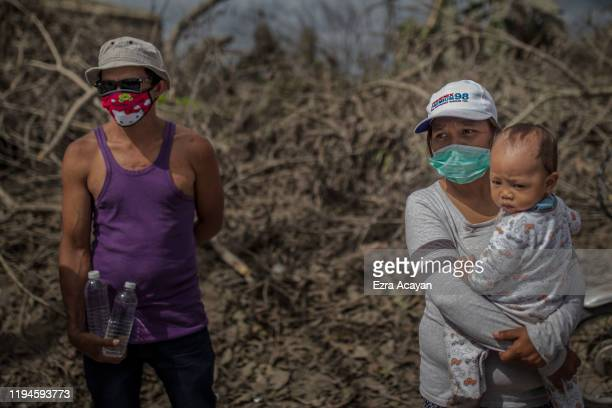 Residents wait at the side of a highway to receive relief goods on January 19 2020 in the outskirts of Tagaytay city Cavite province Philippines The...