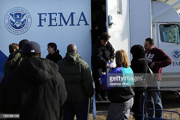 Residents wait for information from FEMA in the heavily damaged Rockaway neighborhood, in Queens where a large section of the iconic boardwalk was...