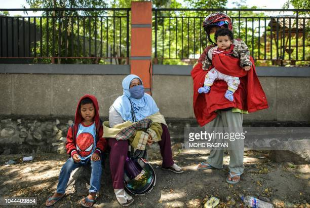 Residents wait for updates on the status of their relatives in Perumnas Balaroa village in Palu Indonesia's Central Sulawesi on October 2 after an...