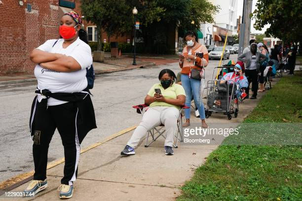 Residents wait in line outside an early voting polling location for the 2020 Presidential election in Atlanta, Georgia, U.S., on Monday, Oct. 12,...