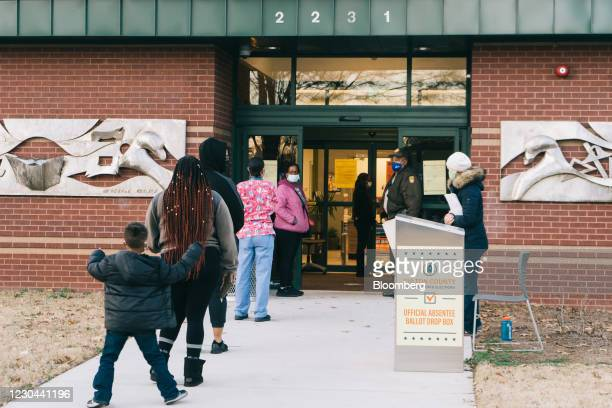Residents wait in line to cast ballots for the Senate runoff elections at a polling location in Atlanta, Georgia, U.S., on Tuesday, Jan. 5, 2021....