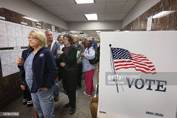 Residents wait in line to pick up a ballot during early voting at the Black Hawk County Courthouse on September 27 2012 in Waterloo Iowa Early voting...