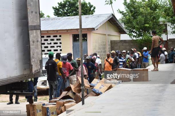 Residents wait in line to receive bags of rice and cooking oil at a World Food Programme distribution site in Port-Salut, Haiti, on Tuesday, Aug. 24,...