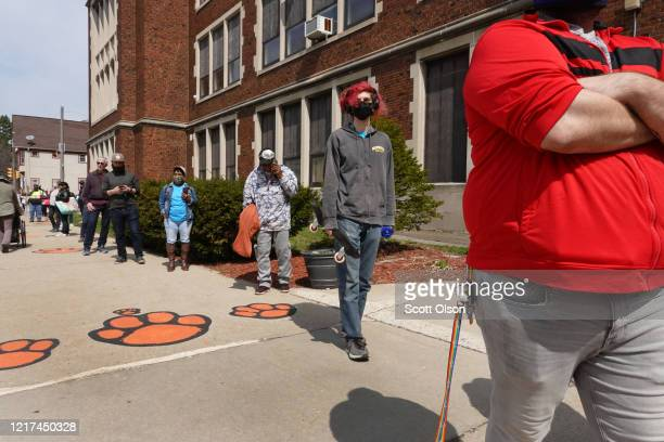 Residents wait in line to vote at a polling place at Riverside University High School on April 07 2020 in Milwaukee Wisconsin Residents waited...