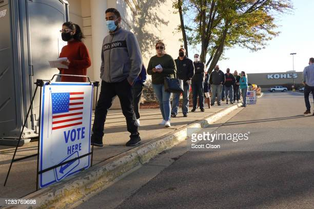 Residents wait in line to vote at a shuttered Sears store in the Janesville Mall on November 03, 2020 in Janesville, Wisconsin. After a...