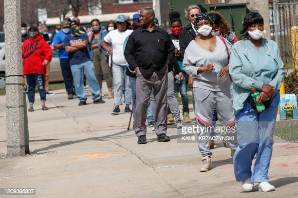 Residents wait in long line to vote in a presidential primary election outside the Riverside High School in Milwaukee Wisconsin on April 7 2020...