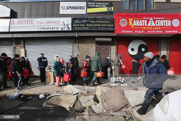 Residents wait on line to collect free gasoline the day after a Nor'Easter storm in the aftermath of Superstorm Sandy in the Rockaway neighborhood on...