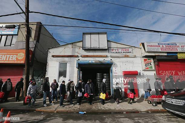Residents wait on line to collect free gasoline the day after a Nor'Easter storm in the aftermath of Superstorm Sandy on November 8, 2012 in the...