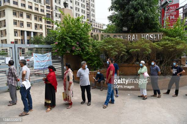 Residents wait outside Mugda Medical College Hospital to get tested for the COVID-19 coronavirus. Bangladesh extends nationwide lockdown measures...