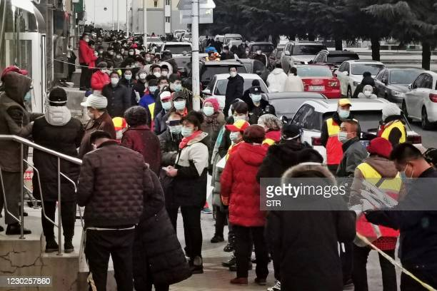Residents wait to be tested for the Covid-19 coronavirus as the city carries out a mass testing program in Dalian, in northeastern China's Liaoning...