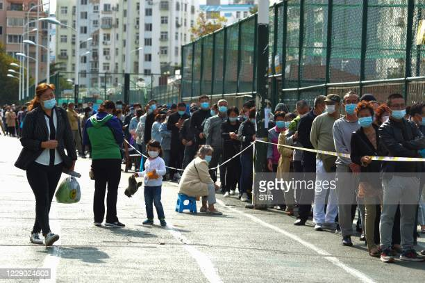 Residents wait to be tested for the COVID-19 coronavirus in Qingdao, in China's eastern Shandong province on October 12, 2020. / China OUT