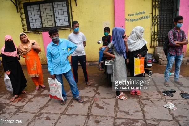 Residents wait to collect their test results for Covid-19 coronavirus ata civic clinic in Dharavi slums, in Mumbai on October 12, 2020. - India's...