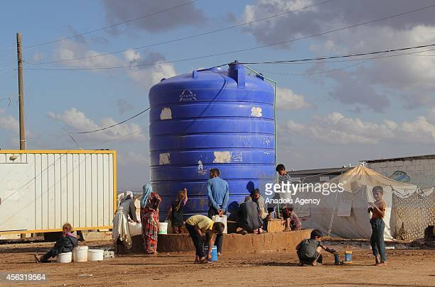 Residents wait to fill their water bins, bottles and buckets with water in front of a water tank at the tent city close to Al Salama border gate in...