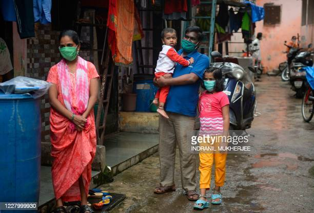 Residents wait to get themselves checked during a COVID-19 coronavirus screening in the Dharavi slum in Mumbai on August 11, 2020.