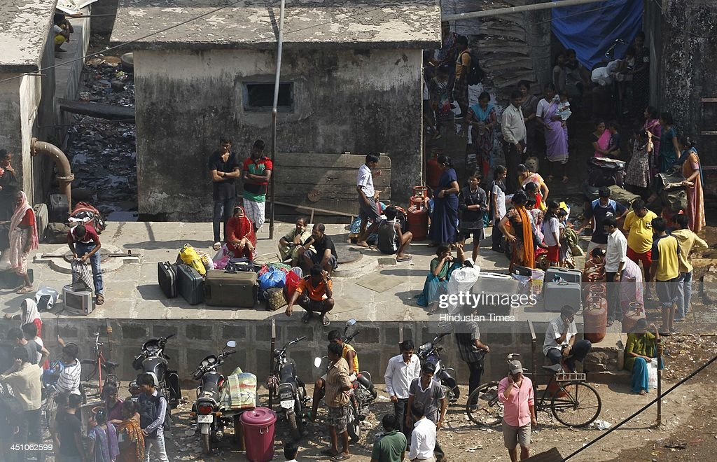 Residents waits outside the slum as fire broke out at Ambedkar Nagar slum, Cuffe Parade on November 21, 2013 in Mumbai, India. Several huts were gutted in a fire that broke out in the settlement. About 10 fire engines and eight water tankers have been rushed to the spot to douse the flames.