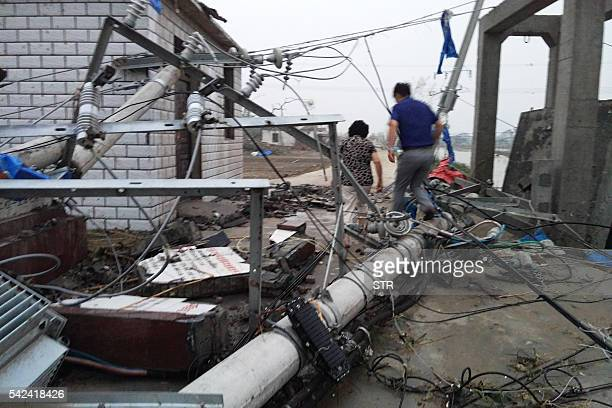 Residents walk across downed power poles after a tornado in Funing in Yancheng in China's Jiangsu province on June 23 2016 xtreme weather including...
