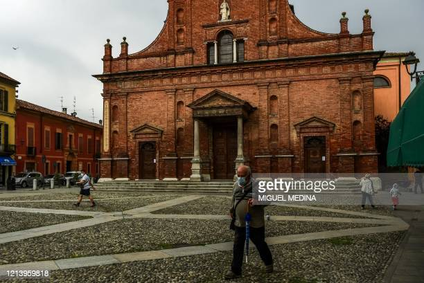Residents walk across Piazza XX Settembre past San Biagio and Santa Maria Immacolata church as rain threatens in Codogno, southeast of Milan, one of...