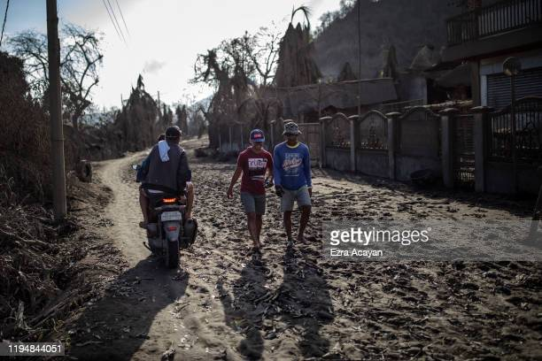 Residents walk along a highway covered in volcanic ash from Taal Volcano's eruption on January 20 2020 in the village of Buso Buso Laurel Batangas...