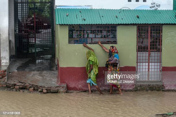 TOPSHOT Residents walk along a house on a flooded street heading to a shelter ahead of the expected landfall of cyclone Amphan in Dacope of Khulna...