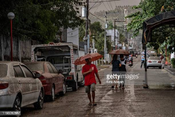 Residents walk along a road covered in ash mixed with rainwater as Taal Volcano erupts on January 12 2020 in Talisay Batangas province Philippines...