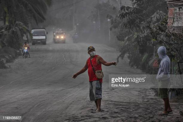 Residents walk along a road covered in volcanic ash from Taal Volcano's eruption on January 13 2020 in Lemery Batangas province Philippines The...