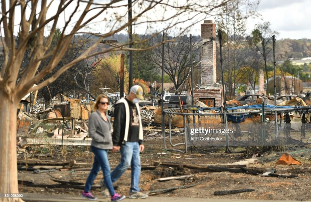 Residents walk along a sidewalk while viewing burned neighborhoods in the Coffey Park area of Santa Rosa, California on October 20, 2017. Residents are being allowed to return to their burned homes on October 20 to grieve and search through remains. Around 5,700 homes and businesses have been destroyed by the fires, the deadliest in California's history. /