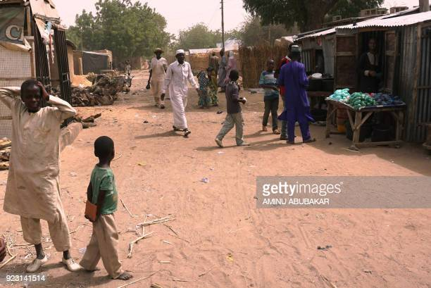 Residents walk along a street in Dapchi Nigeria on February 22 2018 School girls from Dapchi's Government Girls Science and Technical College were...