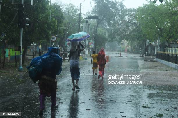 TOPSHOT Residents walk along a street to a shelter ahead of the expected landfall of cyclone Amphan in Digha West Bengal on May 20 2020 India and...