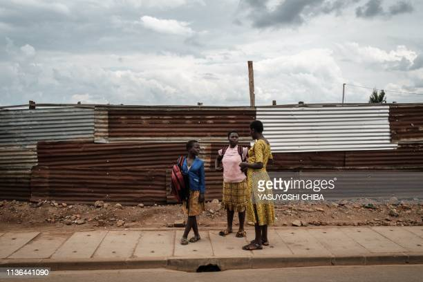 TOPSHOT Residents walk along the fence of an excavation site of pits which were used as mass grave during 1994 Rwandan genocide and hidden under...