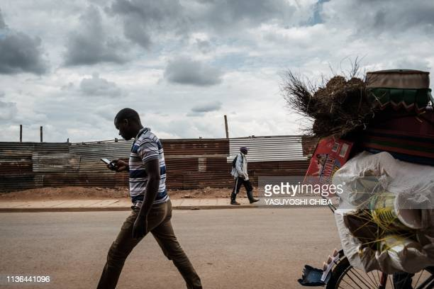 Residents walk along the fence of an excavation site of pits which were used as mass grave during 1994 Rwandan genocide and hidden under houses in...