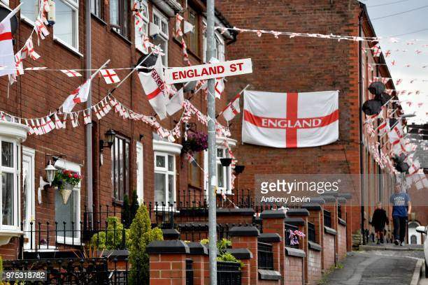 Residents walk along Wales Street in Oldham which local residents have renamed England Street and decorated with flags to celebrate the FIFA World...