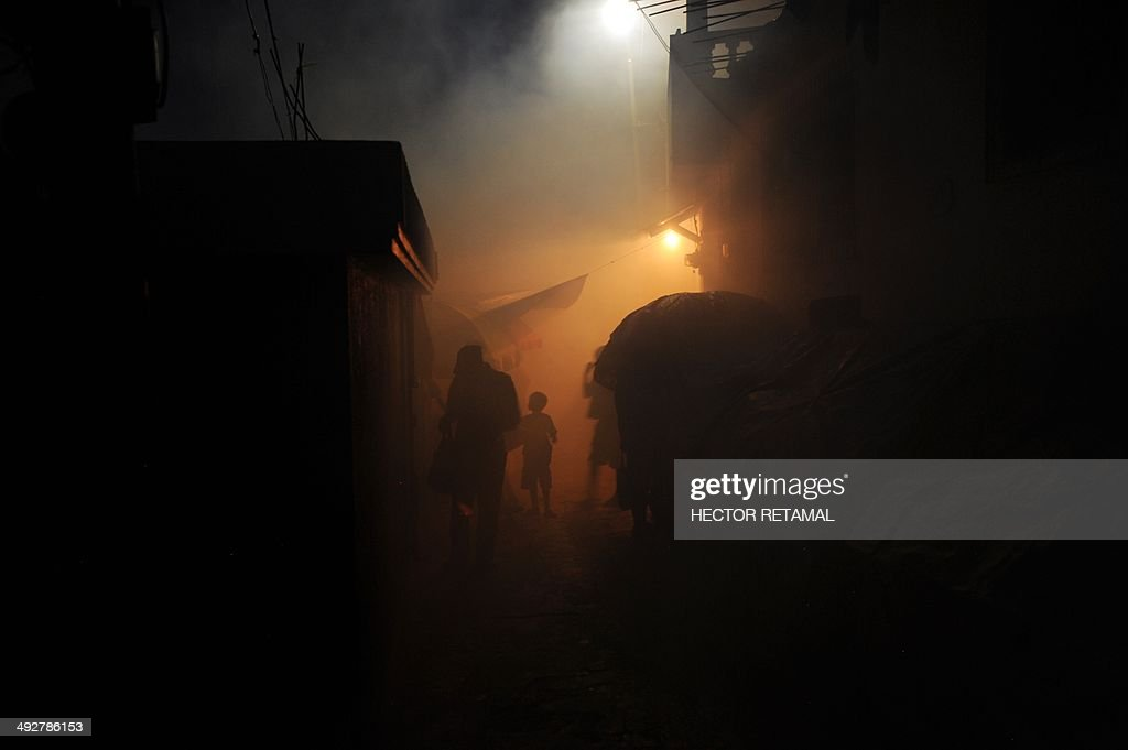 Residents walk amid fumes as workers from Haiti's Ministry of Public Health and Population spray chemicals to exterminate mosquitoes in a neighborhood of Petion Ville in Port-au-Prince on May 21, 2014. A worker said the procedure is to help prevent chikungunya, dengue, malaria and filariose. AFP PHOTO / Hector RETAMAL
