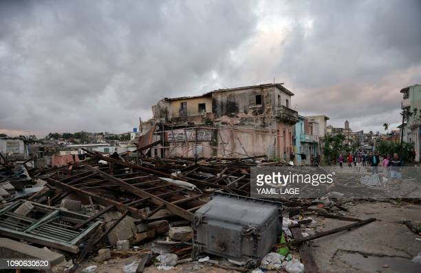 Residents walk amid the debris from their destroyed homes after the passage of a tornado in Havana on January 28 2019 A rare and powerful tornado...