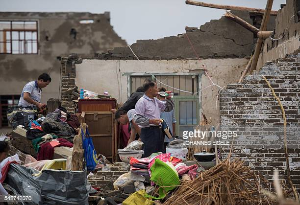 Residents walk amongst the rubble of destroyed houses after a tornado in Funing in Yancheng in China's Jiangsu province on June 24 2016 Survivors...