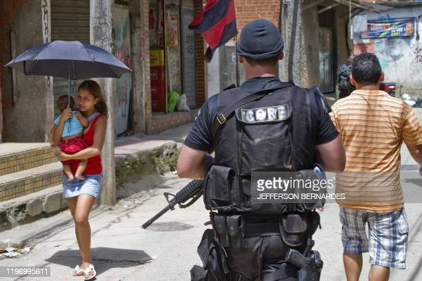 Residents walk as a Coordination of Special Resources policeman patrols Morro do Alemao shantytown on November 29 2010 in Rio de Janeiro Brazil...