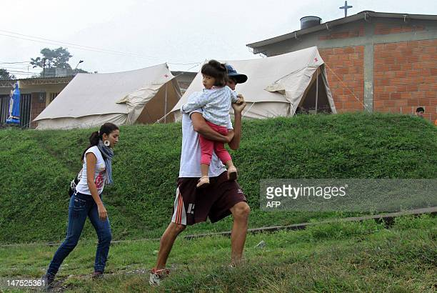 Residents walk at a shelter in Villamaria, Colombia, near the Nevado del Ruiz volcano on July 1, 2012. Authorities ordered on June 30 the preventive...