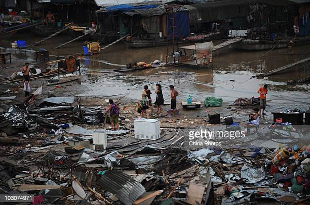 Residents walk at the flooded goods yard and parking lots at the river bank of Longwangmiao water area where the Hanjiang River merges into the...