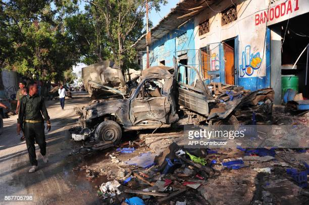Residents walk at the scene of a blast on October 29 a day after two car bombs exploded in Mogadishu Somalia's security ministry said today that...