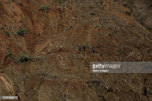 Residents walk at the site where people were believed to have been buried by a landslide on September 18 2018 in in Itogon Benguet province...